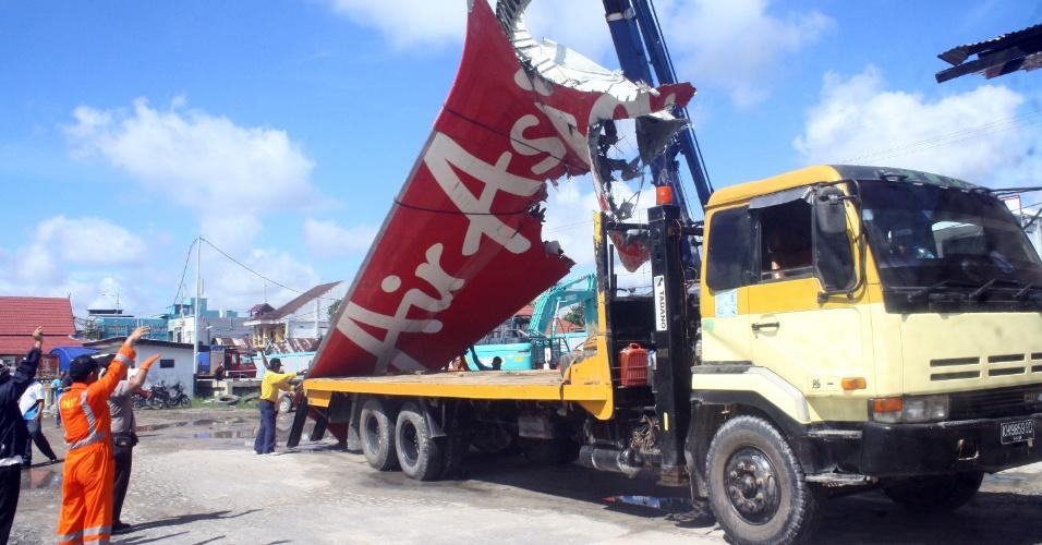 7.fev.2015 - Cauda do voo AirAsia QZ8501 é transportada no porto Kumai, na Indonésia. A peça, encontrada no mês passado no mar de Java, segue para Jacarta. As autoridades do país informaram que resgataram os restos mortais do piloto do avião que caiu com 162 pessoas a bordo no mar de Java em dezembro e que localizaram o corpo do copiloto