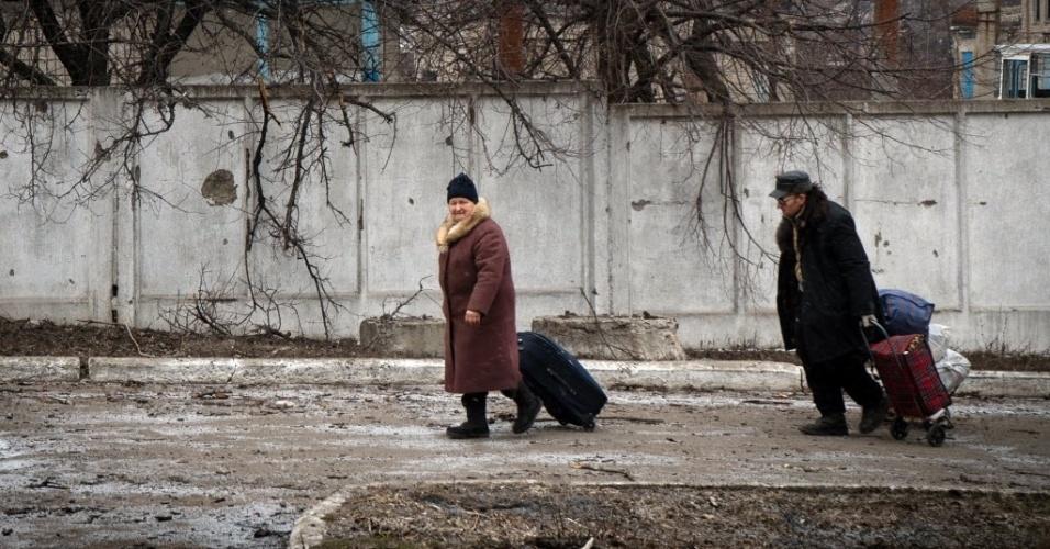 7.fev.2015 - Moradores carregam pertences pessoais por ruas da cidade de Vuglegirsk, na região de Donetsk, no leste da Ucrânia. As autoridades ucranianas afirmaram que há razões para ser otimista sobre um acordo de paz com a Ucrânia, mas também alertou contra iniciativas para armar o exército de Kiev, e culpou os Estados Unidos e a Europa por