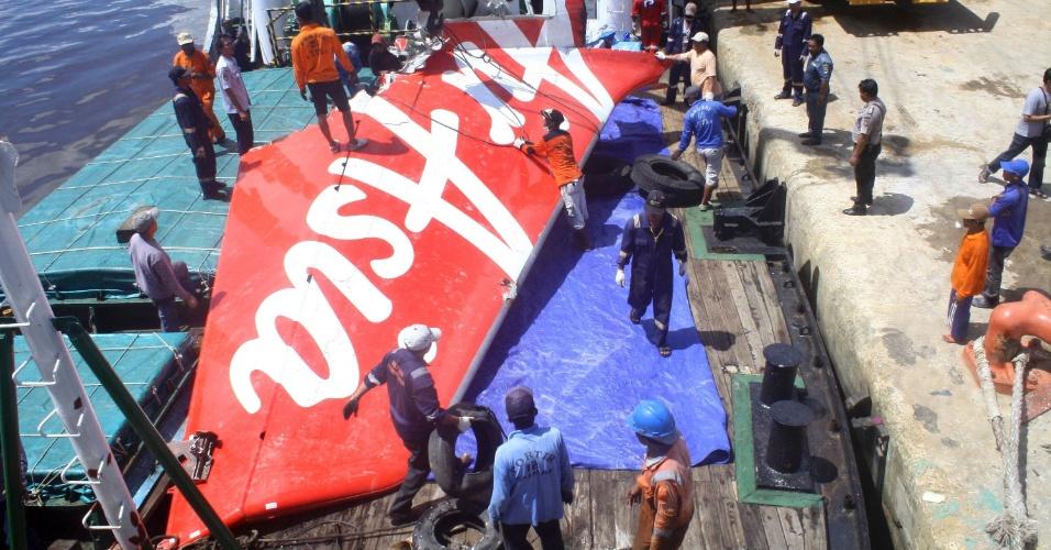 7.fev.2015 - Trabalhadores carregam a cauda do voo AirAsia QZ8501 no porto Kumai, na Indonésia. A peça, encontrada no mês passado no mar de Java, segue para Jacarta. As autoridades da Indonésia informaram que resgataram os restos mortais do piloto do avião que caiu com 162 pessoas a bordo no mar de Java em dezembro e que localizaram o corpo do copiloto