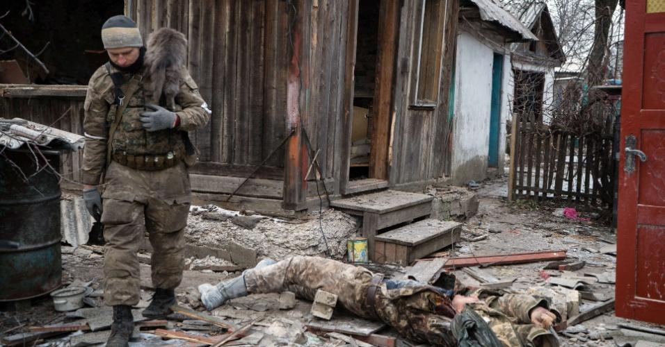 7.fev.2015 - Um rebelde pró-Rússia carrega gato ao passar por soldado ucraniano morto em Vuglegirsk, na região de Donetsk, no leste da Ucrânia. As autoridades ucranianas afirmaram que há razões para ser otimista sobre um acordo de paz com a Ucrânia, mas também alertou contra iniciativas para armar o exército de Kiev, e culpou os Estados Unidos e a Europa por