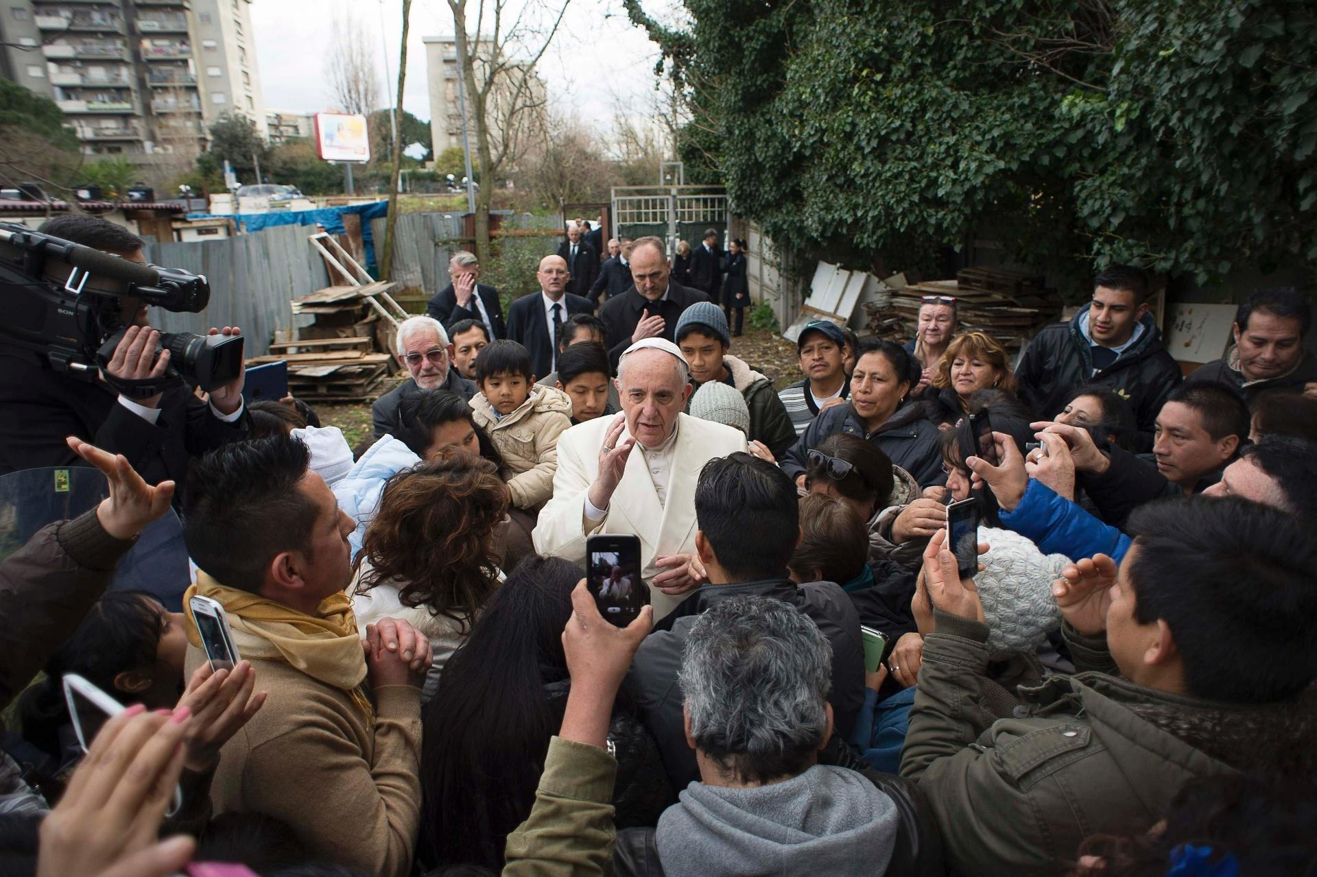 8.fev.2015 - O Papa Francisco conversa com moradores de uma comunidade carente nos arredores de Roma, na Itália, durante uma visita surpresa. O pontifício estava a caminho de uma visita a uma paróquia da área operária de Tiburtina quando mudou a rota para conhecer a favela que ele havia ouvido falar