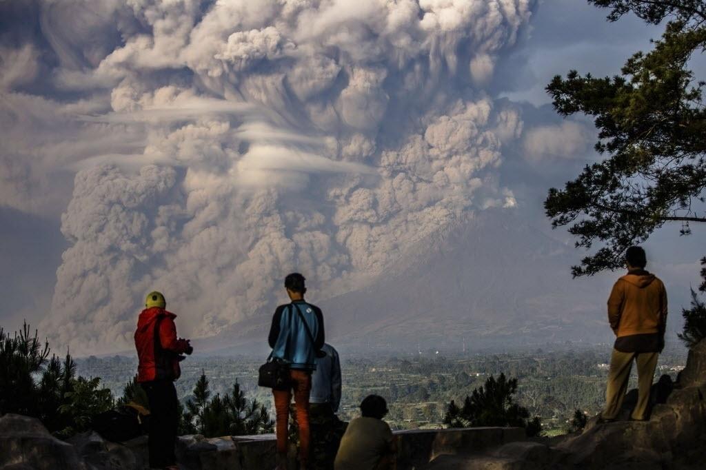 9.fev.2015 - Homens observam nesta segunda-feira (9) nuvem de fumaça expelida pelo vulcão Sinabung, em Karo, na província de Sumatra do Norte, na Indonésia