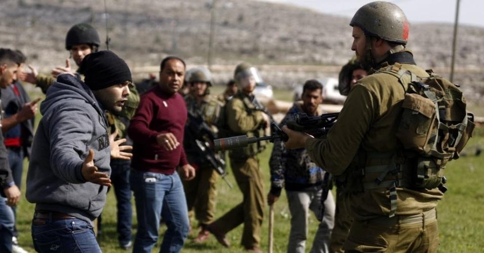 9.fev.2015 - Manifestante palestino discute nesta segunda-feira (9) com um soldado israelense durante um protesto contra o confisco de terras para assentamentos judeus, na aldeia de Silwad, na Cisjordânia