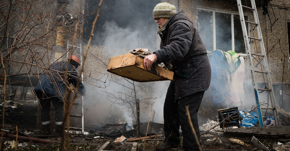 9.fev.2015 - Moradores tentam salvar seus pertences de um prédio que foi atingido por um bombardeio no combate entre rebeldes pró-Rússia e forças ucranianas, em Donetsk, no leste da Ucrânia, nesta segunda-feira (9). O presidente dos EUA, Barack Obama, acusou a Rússia de ter violado todos os compromissos assumidos em setembro passado para levar a paz à Ucrânia
