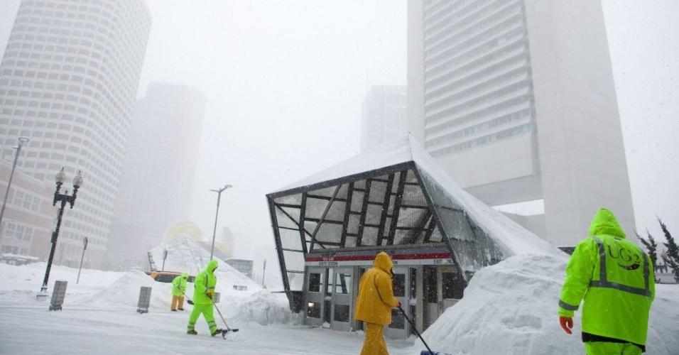 9.fev.2015 - Trabalhadores limpam a neve em torno de uma estação de metrô em Boston, no Estado americano de Massachusetts, nesta segunda-feira (9). A cidade foi atingida pela terceira grande tempestade de neve em três semanas, chegando a 40 centímetros de neve acumulada, segundo autoridades
