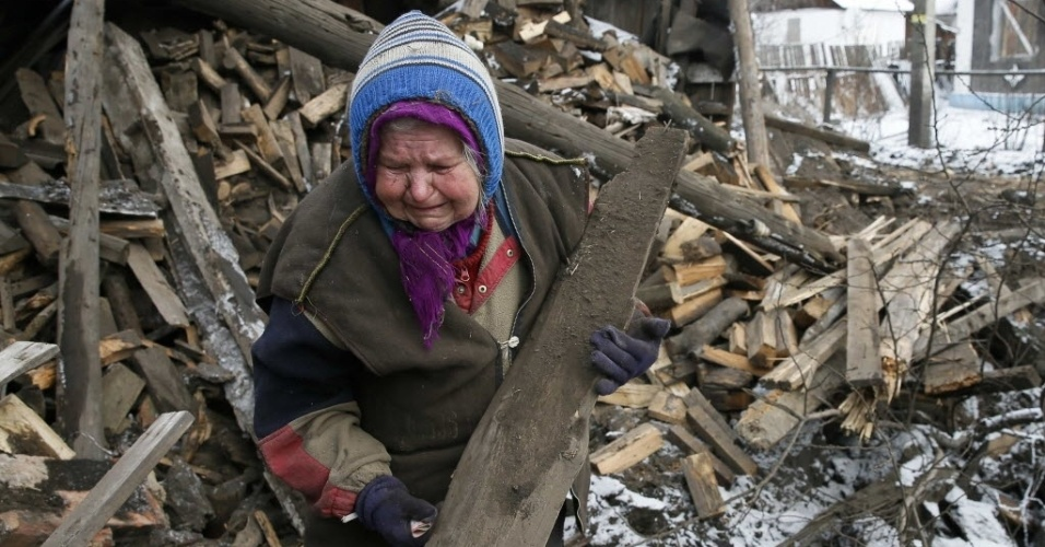 10.dez.2015 - Moradora remove pedaços de madeira da frente da sua casa, que foi danificada durante confronto entre rebeldes pró-Rússia e forças ucranianas, na cidade de Horlivka, no leste da Ucrânia, nesta terça-feira (10)