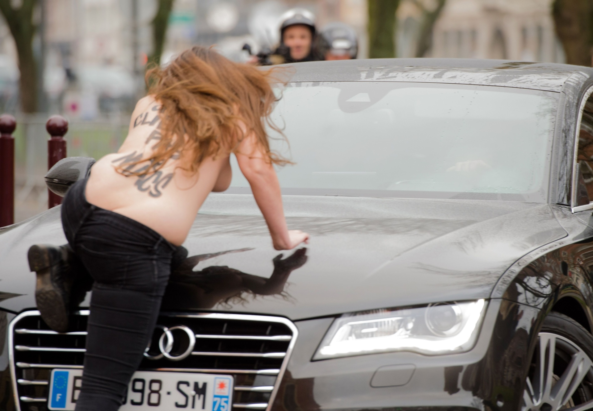 10.fev.2015 - Ativista do Femen sobe no carro do ex-chefe do FMI Dominique Strauss-Kahn, que chegou para ser julgado por exploração da prostituição, em Lille, no norte da França, nesta terça-feira (10). Três mulheres que faziam topless pularam no carro de Strauss-Kahn e foram detidas pela polícia