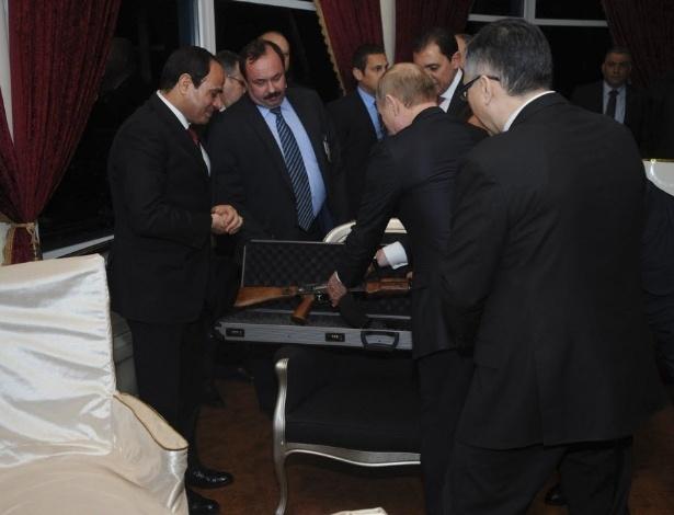O presidente russo, Vladimir Putin, presenteia o presidente egípcio, Abdel Fattah al-Sisi (à esquerda), com um fuzil kalashnikov AK-47