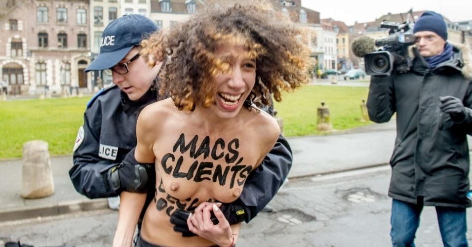 10.fev.2015 - Policial impede ativista do grupo Femen de protestar em frente ao carro do ex-chefe do FMI Dominique Strauss-Kahn, que chegou para ser julgado por acusações de exploração da prostituição, em Lille, no norte da França, nesta terça-feira (10). Três mulheres que faziam topless e pularam no carro de Strauss-Kahn foram rapidamente cercadas pela polícia