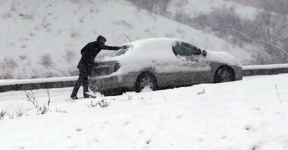 11.fev.2015 - Homem retira neve de cima do veículo em Ancara, na capital da Turquia, nesta quarta-feira (11)