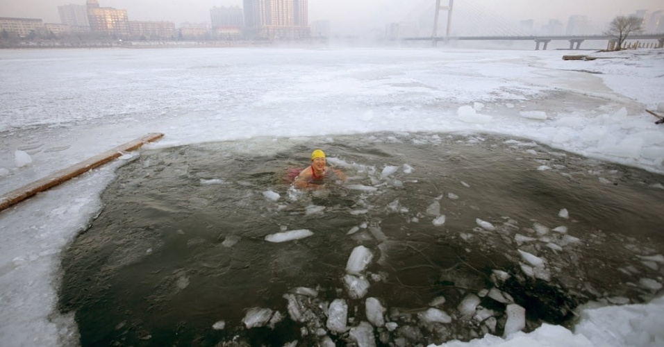 11.fev.2015 - Nadadora quebra a superfície congelada do rio Songhua em Jilin, na China, e enfrenta águas geladas nesta quarta-feira (11)