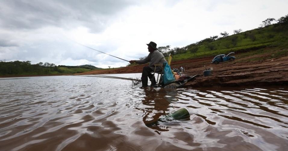 11.fev.2015 - A dona de casa Ana Maria de Souza, 64, pesca na represa Cachoeira, na cidade de Piracaia, no interior de São Paulo. O local é o 4º volume morto do sistema Cantareira