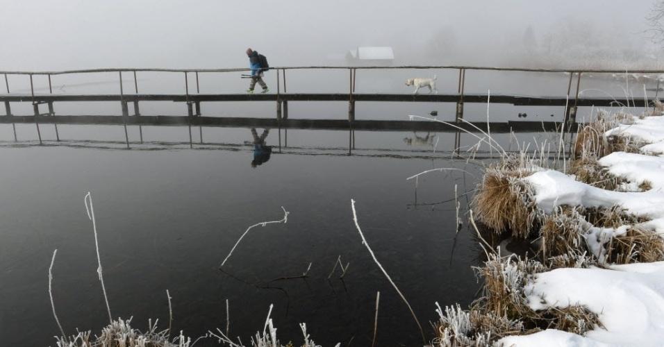 12.fev.2015 - Homem atravessa ponte no lago Kochelseem, perto da vila Schlehdorf, no sul da Alemanha, nesta quinta-feira (12). De acordo com a previsão meteorológica, uma frente fria chegará na região