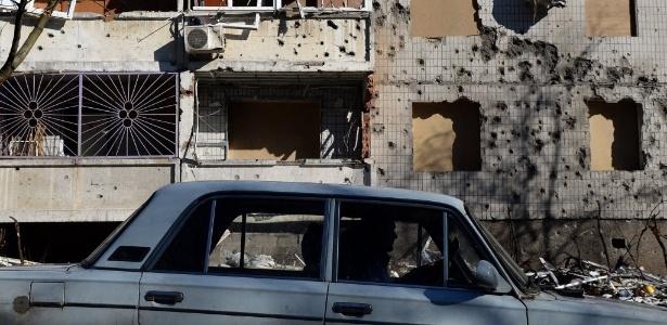 Motorista passa por prédio destruído por bombardeio em Donetsk, no leste da Ucrânia