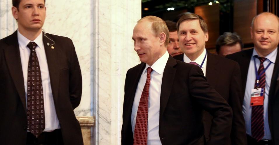 12.fev.2015 - Vladimir Putin, presidente da Rússia, deixa salão de reunião que trata da crise com a Ucrânia nesta quinta-feira (12) em Minsk, capital de Belarus, que faz fronteira com os dois países em conflito. Um acordo foi alcançado após negociações durante toda a noite, e inclui um cessar-fogo que entraria em vigor em 15 de fevereiro, seguido pela retirada das armas pesadas