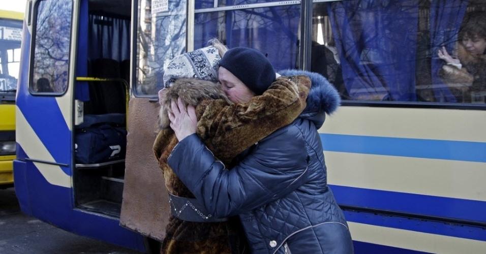 13.fev.2015 - Mulheres se despedem antes de serem transportadas de Donetsk, na Ucrânia, para a Rússia, nesta sexta-feira (13). A União Europeia (UE) prepara novas sanções a Rússia e aos separatistas, caso o cessar-fogo na Ucrânia, acordado em Minsk, não seja respeitado