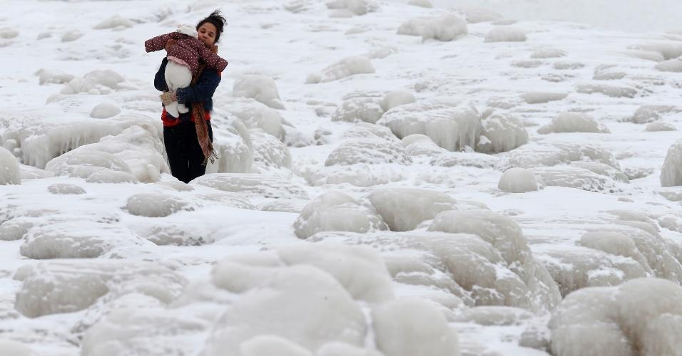 17.fev.2015 - Uma mulher carrega um bebê enquanto passa por um labirinto de pedaços gigantes de gelo ao longo do lago Michigan, em Chicago, Illinois (EUA), nesta terça-feira (17). Uma tempestade de inverno paralisou grande parte do leste dos EUA nesta terça, fechando escritórios federais em Washington