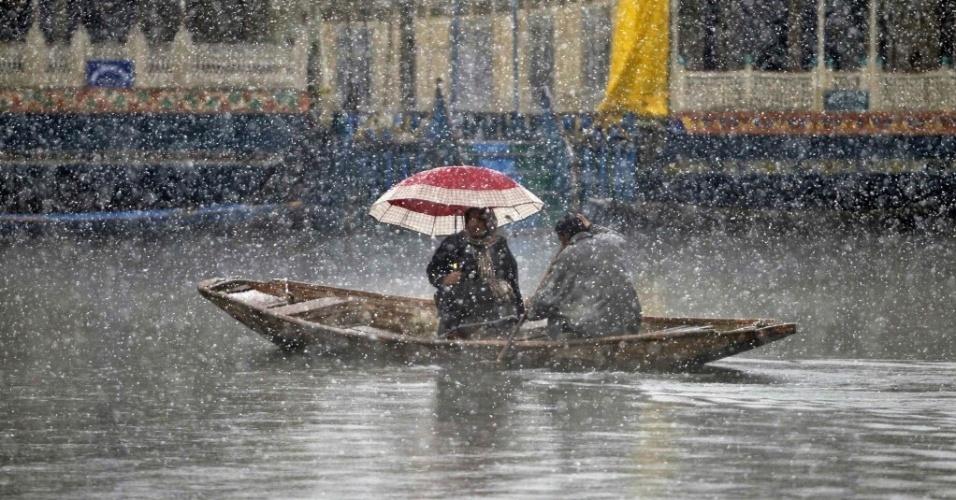 19.fev.2015 - Indiana se protege com um guarda-chuva enquanto navega no lago Dal durante uma tempestade de neve em Srinagar, na Índia, nesta quinta-feira (19)