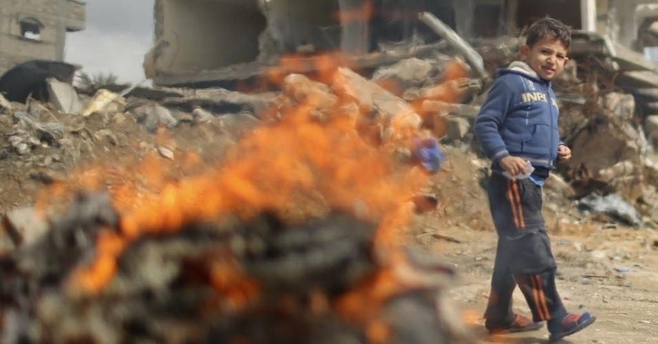 19.fev.2015 - Menino palestino caminha ao lado de uma fogueira perto das ruínas da casa de sua família, que foi destruída por bombardeios israelenses durante confronto com o Hamas entre julho e agosto do ano passado, na Cidade de Gaza, nesta quinta-feira (19)