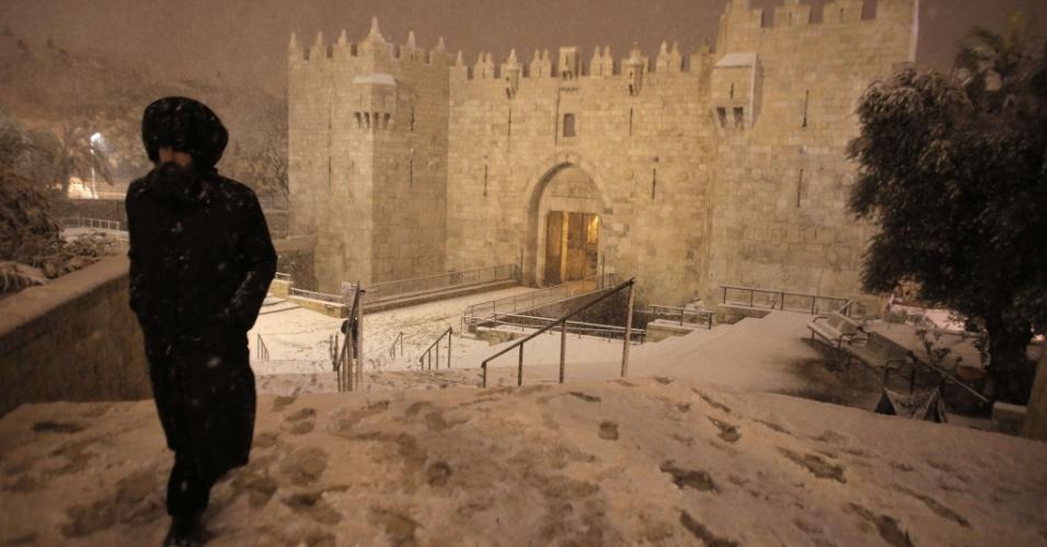 19.fev.2015 - Um judeu ultra-ortodoxo caminha próximo ao Portão de Damasco, na antiga cidade de Jerusalém, após uma nevasca atingir a capital israelense, nesta quinta-feira (19)