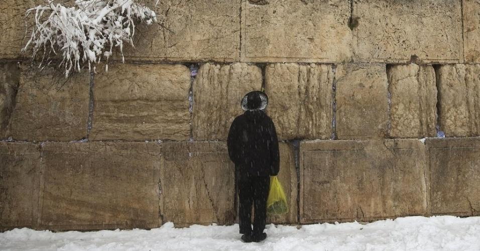 20.fev.2015 - Devoto reza no Muro das Lamentações sob tempestade de neve na Cidade Velha de Jerusalém, em Israel, nesta sexta-feira (20). As escolas da cidade foram fechadas por conta do mau tempo