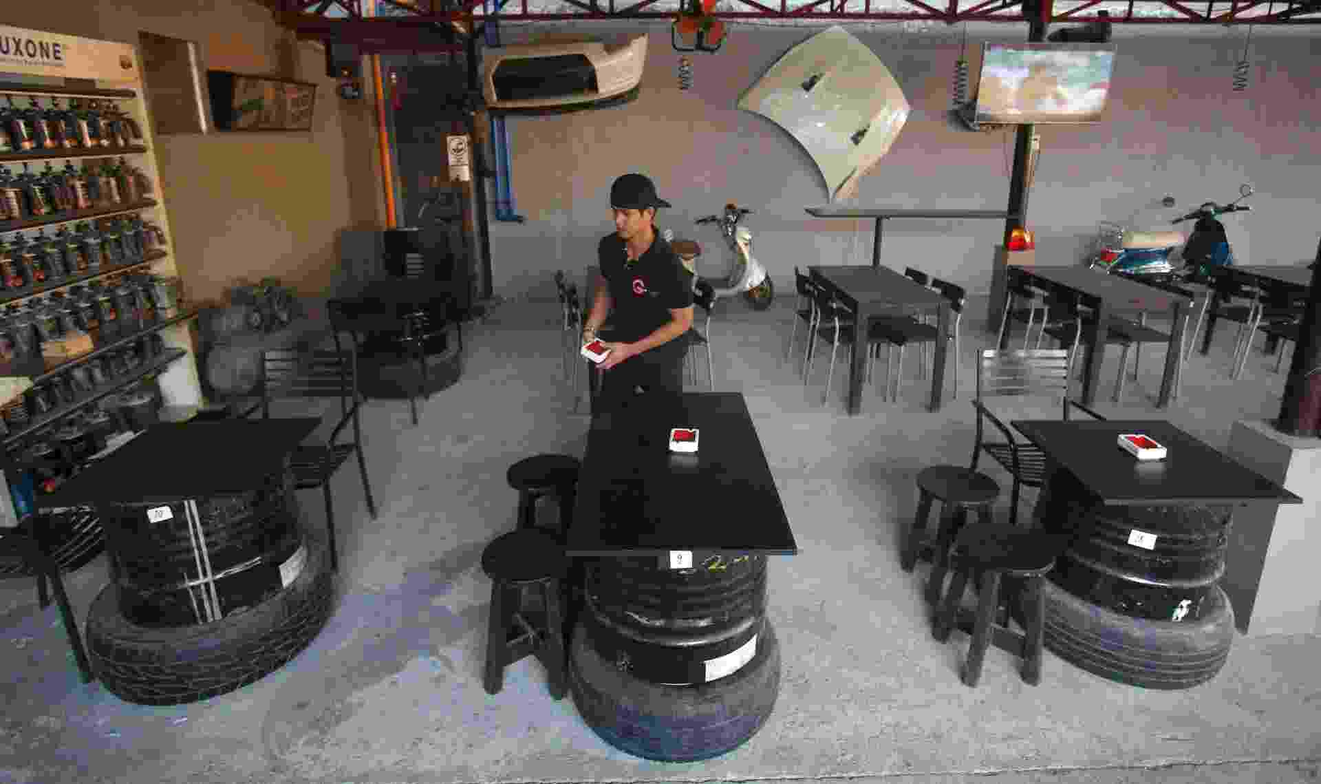 20.fev.2015 - Garçom caminha entre mesas feitas com antigos barris de petróleo em bar, em Parañaque, nas Filipinas - Erik de Castro/Reuters