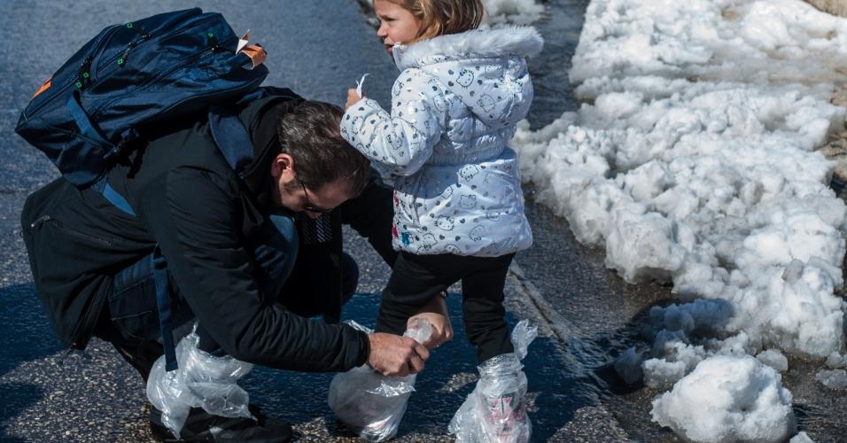 20.fev.2015 - Pai ajuda filha a proteger os sapatos com sacos plásticos na parte oeste da Cidade Antiga de Jerusalém, em Israel. Regiões do país foram cobertas por neve após uma forte tempestade