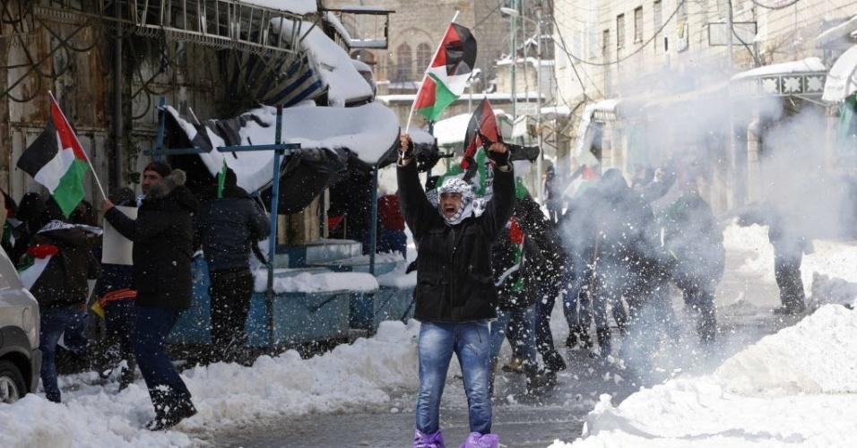 20.fev.2015 - Palestinos protestam contra o fechamento da rua Shuhada, na cidade de Hebron, na Cisjordânia, nesta sexta-feira (20). Dezenas de manifestantes, incluindo ativistas estrangeiros, protestaram no 21º aniversário do fechamento da rua, feito pelo Exército israelense em 1994. O o acesso ao local foi proibido depois de um massacre na mesquita da cidade por Baruch Goldstein, um colono israelense, matando 29 fiéis palestinos