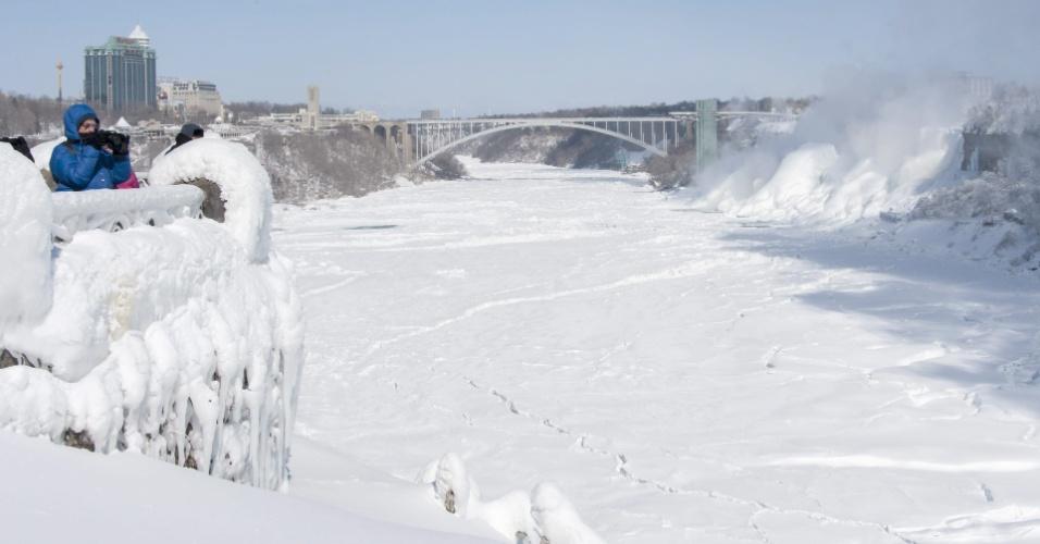 20.fev.2015 - Turistas fotografam o rio e as cataratas do Niágara, no Canadá. Com o frio extremo, as águas das Cataratas do Niágara, que se situam na fronteira entre Estados Unidos e Canadá, ficaram congeladas e as temperaturas atingiram a marca dos -14ºC
