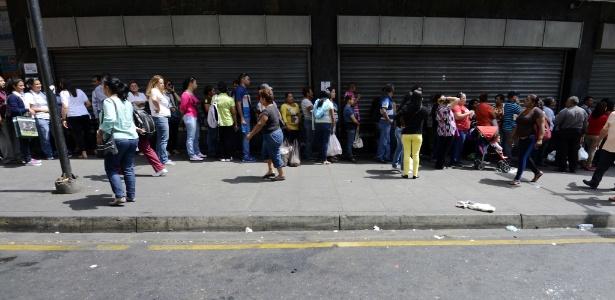 Consumidores fazem fila do lado de fora de um supermercado em Caracas