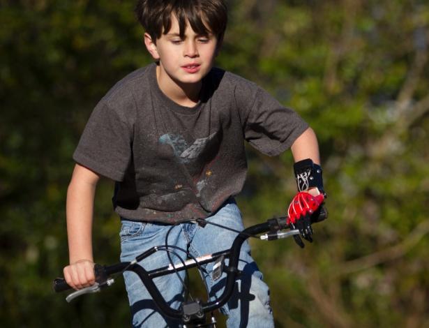"""Ethan Brown, 8, anda de bicicleta com sua prótese de mão feita em impressora 3D. """"Parece com o Homem-Aranha"""", diz"""