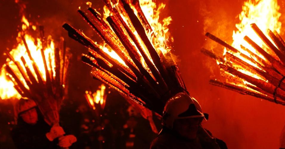 22.fev.2015 - Participantes da festa suíça Chienbaese levam tochas de madeira em chamas nas celebrações do Carnaval em Liestal, próximo à Basileia