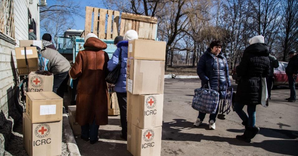 23.fev.2015 - Habitantes de Avdiyivka, cidade próxima a Donetsk, recebem caixas de ajuda humanitária do Comitê Internacional da Cruz Vermelha, nesta segunda-feira (23). A cidade está sob controle do exército ucraniano