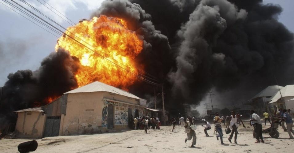 23.fev.2015 - Moradores correm após uma explosão em um posto de gasolina e de armazenamento de combustível perto do mercado de Bakara, em Mogadíscio, na Somália, nesta segunda-feira (23)