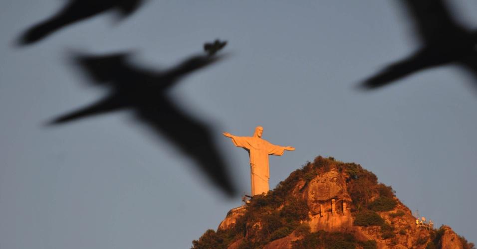 23.fev.2015 - Pássaros voam próximos ao monumento do Cristo Redentor em foto tirada do bairro do Botafogo, na zona sul do Rio de Janeiro, na manhã desta segunda-feira (23). A máxima prevista para a cidade é de 35ºC