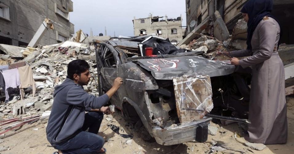 24.fev.2015 - Artistas palestinos pintam nesta terça-feira (24) carros destruídos por bombardeios israelenses durante confronto com o Hamas entre julho e agosto do ano passado, em Rafah, no sul da faixa de Gaza. A iniciativa busca transformar vestígios dos combates em lembranças para os proprietários