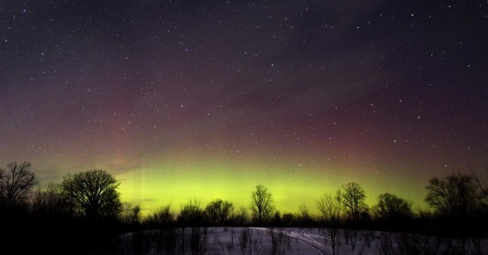 24.fev.2015 - Brilho da aurora boreal ilumina o horizonte na região de Kawartha Lakes, no sul de Ontário, no Canadá. O fenômeno natural raramente acontece na região