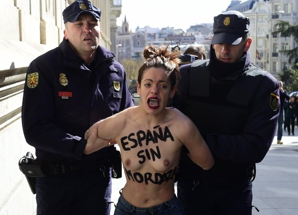 24.fev.2015 - Dois policiais apreendem uma ativista do Femen, que tem escrito no peito