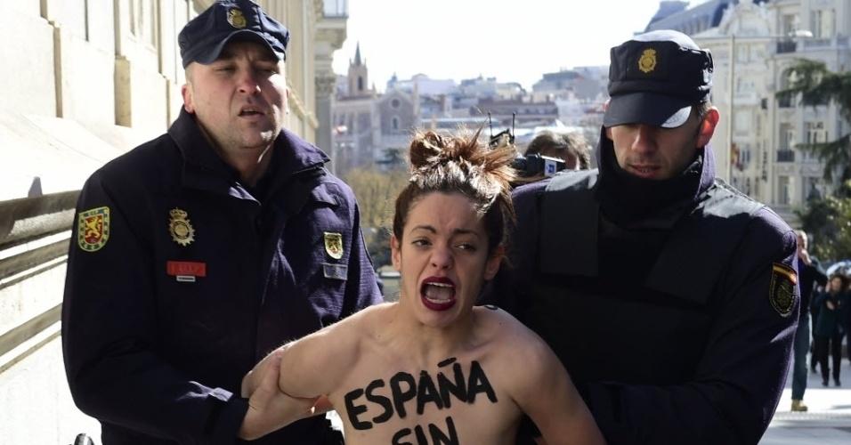 """24.fev.2015 - Dois policiais apreendem uma ativista do Femen, que tem escrito no peito """"Espanha sem mordaça"""", durante um protesto que reivindica o direito de se manifestar, em frente ao Congresso espanhol, em Madri, nesta terça-feira (24). A """"Lei da Mordaça"""" pune protestos não autorizados com multas pesadas e permite a expulsão sumária de imigrantes que tentam entrar ilegalmente no país"""