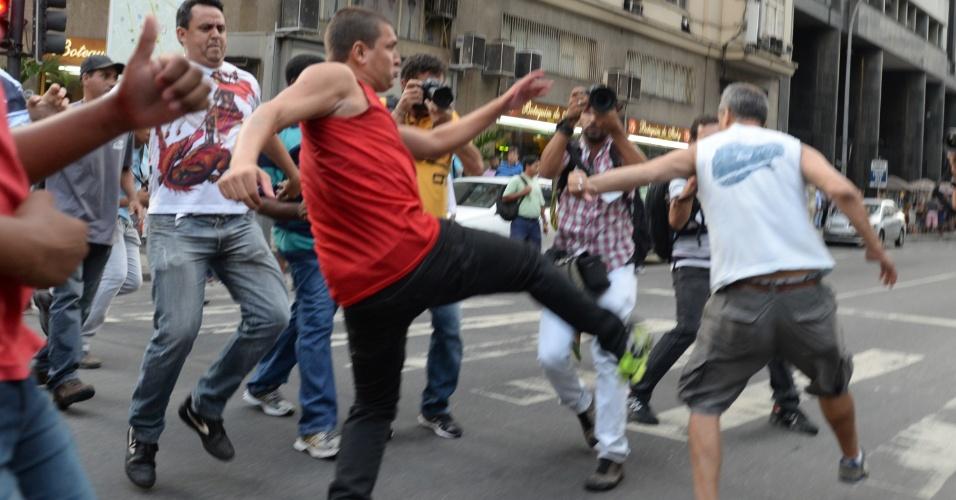 24.fev.2015 - Manifestantes que participavam de ato em defesa da Petrobras, a maioria usando camisetas da Central Única dos Trabalhadores (CUT), repeliram com violência outro grupo de ativistas, que chegaram com cartazes cobrando investigações na estatal. A manifestação aconteceu na tarde desta terça-feira (24) em frente à sede da ABI (Associação Brasileira de Imprensa), no centro do Rio de Janeiro