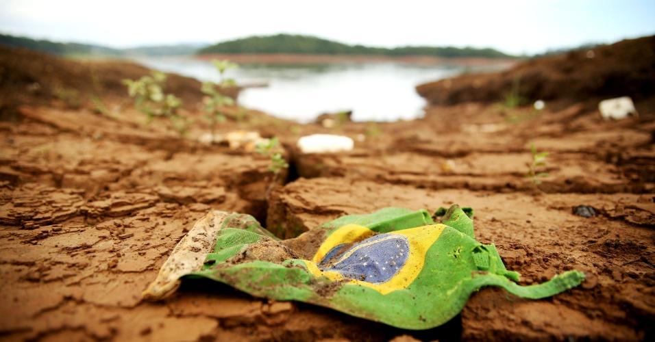 25.fev.2015 - Pedaço de bandeira do Brasil fica visível sobre o solo ca represa Atibainha, na cidade de Nazaré Paulista (SP), que integra o Sistema Cantareira, principal manancial de São Paulo. O sistema voltou a receber chuva e chegou ao 20º dia consecutivo de alta, segundo apontou o boletim da Companhia de Saneamento Básico do Estado de São Paulo (Sabesp), publicado nesta quarta-feira (25). Os reservatórios que compõem o sistema atingiram 10,8% da capacidade