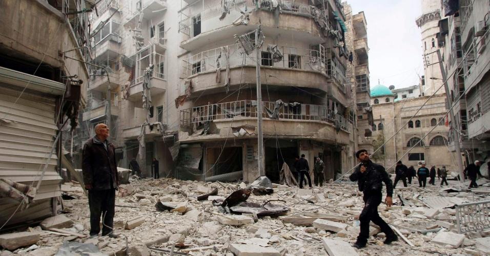 26.fev.2015 - Moradores observam os danos em prédios e ruas de local atingido, segundo guerrilheiros rebeldes sírios, por duas bombas-barril lançadas por forças leais ao ditador da Síria, Bashar Assad, no bairro de al-Shaar de Aleppo, nesta quinta-feira (26)