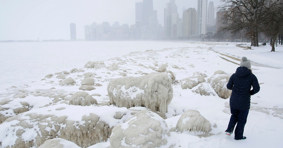 26.fev.2015 - Mulher caminha por montes de neve e gelo ao longo do lago Michigan, em Chicago, Illinois (EUA), nesta quinta-feira (26)