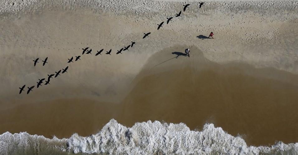 26.fev.2015 - Pássaros sobrevoam pescador na praia de São Conrado, no Rio de Janeiro