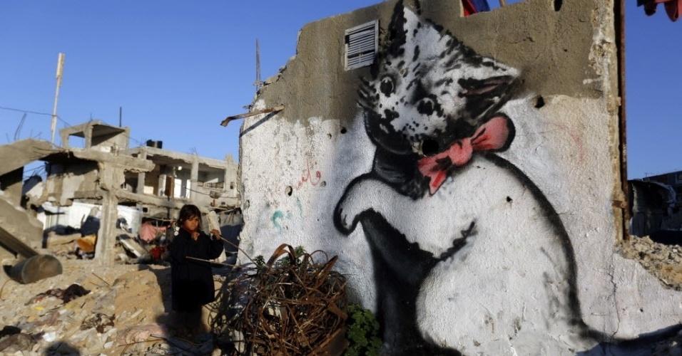 27.fev.2015 - Criança palestina para ao lado de um muro com uma pintura de gato, que pode ter sido feita pelo artista britânico Banksy, sobre as ruínas de uma casa destruída durante confrontos entre Israel e o Hamas em julho e agosto de 2014, em Beit Hanun, na faixa de Gaza