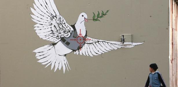 Grafite de Banksy feito em Belém, na Cisjordânia, mostra uma pomba da paz com colete à prova de balas - Ammar Awad/Reuters