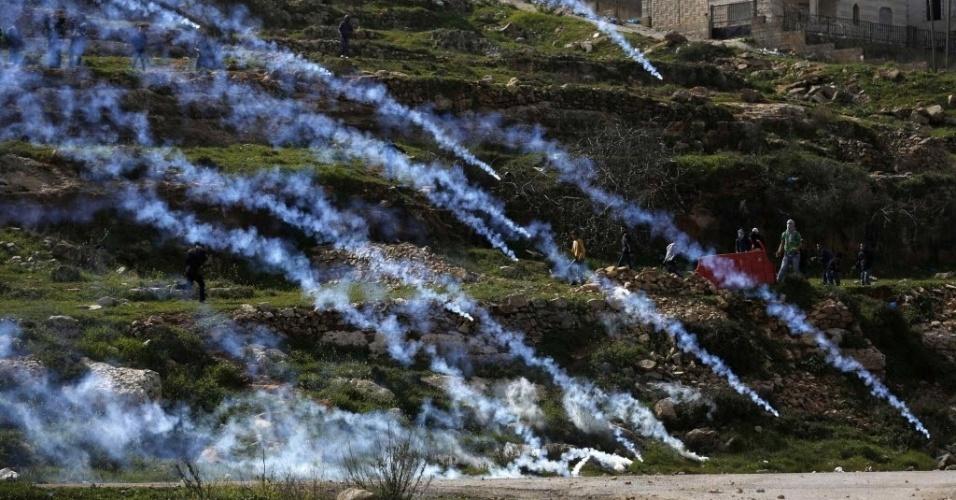 28.fev.2015 - Bombas de gás lacrimogêneo disparadas por soldados israelenses caem sobre manifestantes palestinos durante confrontos perto da prisão Ofer de Israel, nos arredores de Ramallah, na Cisjordânia