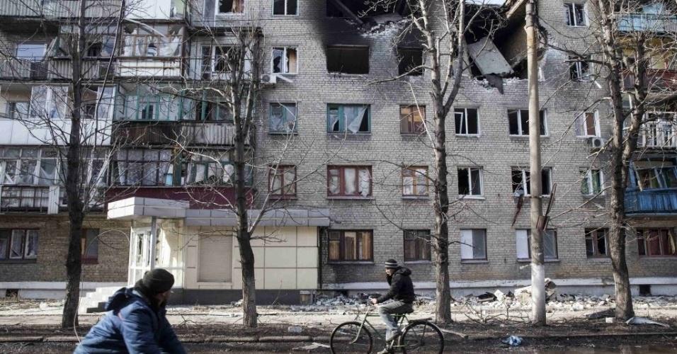 28.fev.2015 - Ciclista observa o topo de um edifício em Debaltseve, na Ucrânia, destruído após confronto entre o Exército nacional e separatistas pró-Rússia. A cidade foi tomada pelos rebeldes