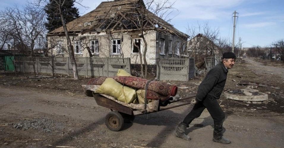 28.fev.2015 - Homem passa por uma casa em ruínas puxando carrinho de mão carregado com tapetes, em Debaltseve, leste da Ucrânia. A cidade sofre os efeitos do confronto entre o Exército ucraniano e rebeldes separatistas pró-Rússia