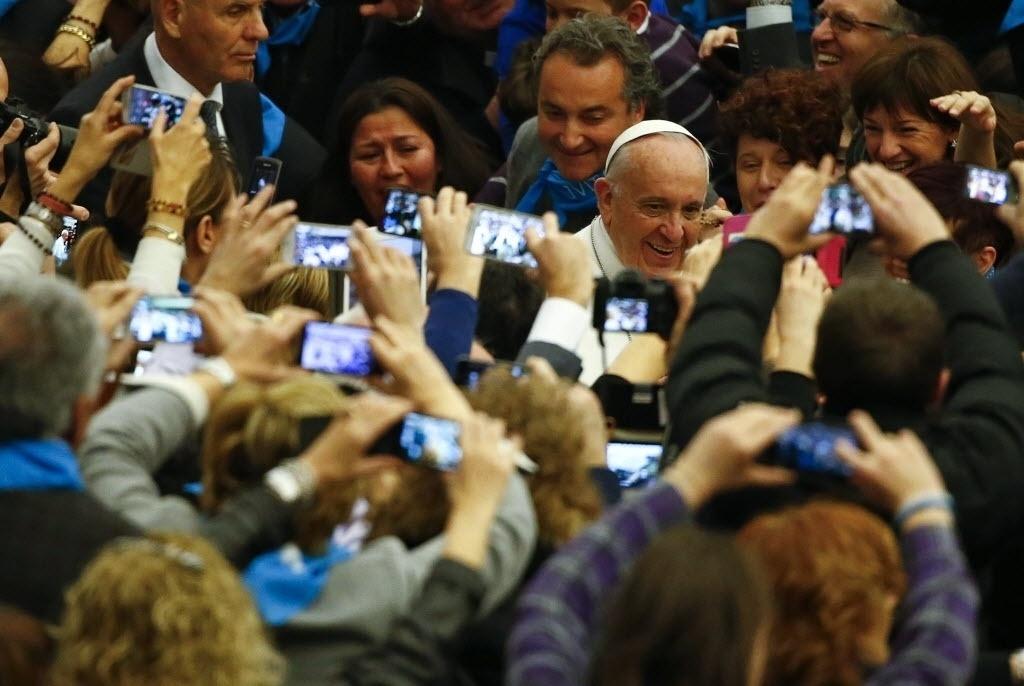 28.fev.2015 - Multidão tira fotos do papa Francisco, que chega para liderar uma audiência especial com os membros da confederação de cooperativas italianas na sala Paulo 6º, no Vaticano